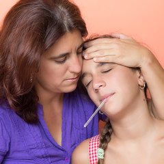 Hispanic mother taking the temperature of her sick  daughter