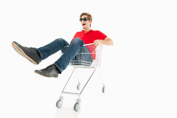 Shopaholic. Cheerful young man riding shopping cart