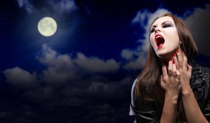 Vampire girl on night sky