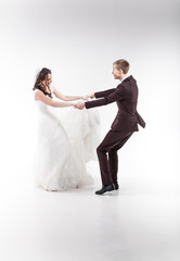 Newlywed couple holding hands and dancing
