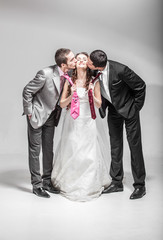 Two men kissing bride in cheek