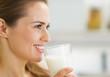 Leinwandbild Motiv Happy young housewife drinking milk