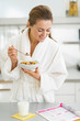 Happy young housewife in bathrobe having healthy breakfast