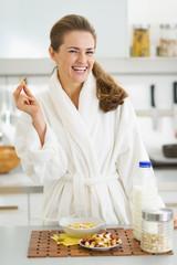 Happy young woman in bathrobe having healthy breakfast