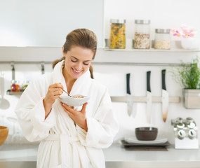 Smiling young housewife having healthy breakfast in  kitchen