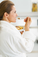 Young housewife in bathrobe having healthy in kitchen