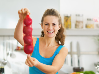 Happy young woman showing bunch of red onions
