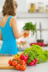 Closeup on vegetables on table and housewife in background