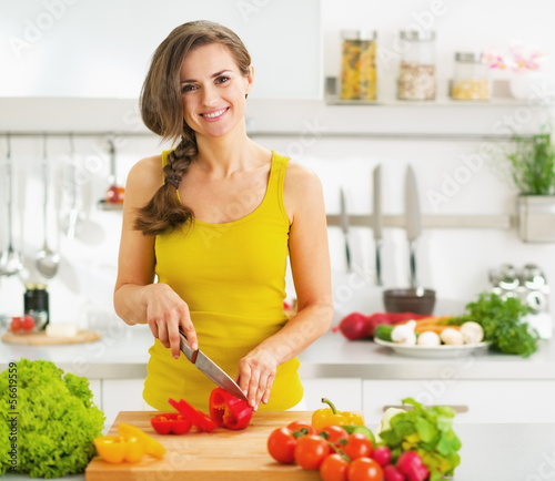 Happy young woman cutting fresh vegetable salad