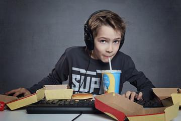 enfant jouant à l'ordinateur buvant et mangeant