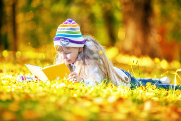 Beautiful girl reading the book in park