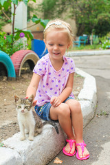 Pretty Little beautiful girl plays with a homeless small kitten