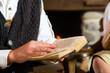 Junger Mann in einer Almhütte liest Bibel