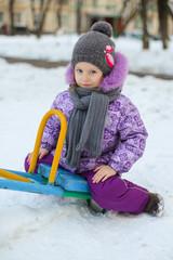 Portrait of Little cute happy girl having fun in the snow on a