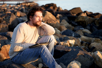 Man relaxing on beach while working with tablet during sunset