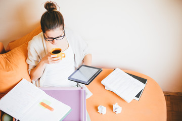 Young woman studying and drinking coffee