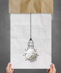 hand pulling light bulb crumpled paper out of recycle envelope