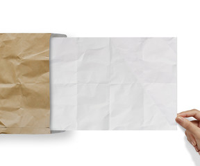 hand pulling crumpled paper from recycle envelope
