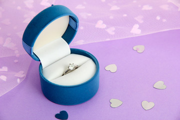 Beautiful box with wedding ring on purple background