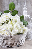 Wicker basket of white roses on rustic wooden table