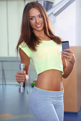 Pretty sporty girl photographing herself in mirror at phone in