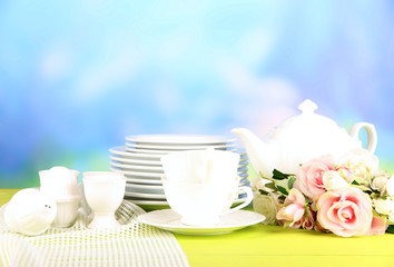 Lots beautiful dishes on wooden table on natural background