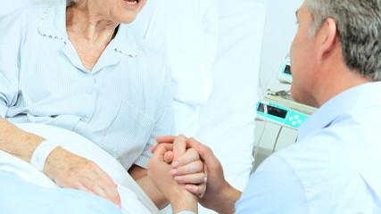 Caring Son Reassuring Nervous Mother Hospital Bed