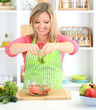 Happy smiling woman in kitchen preparing vegetable salad