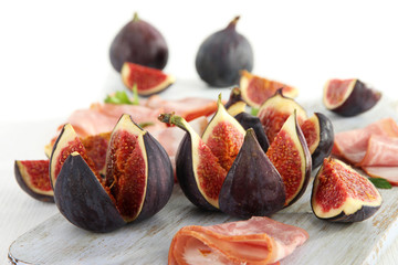 Tasty figs with ham on white wooden table