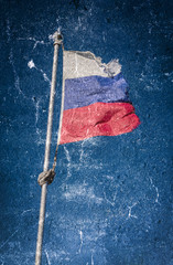 Tattered russian flag over blue sky. Grunge textured.