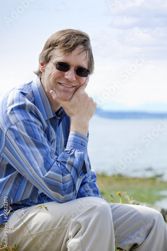 Handsome Causcasian man in forties relaxing by lake side