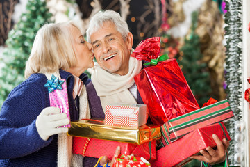 Woman Kissing Man Holding Christmas Presents