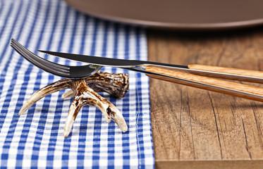 Hirschgeweih als Besteckbänkchen auf blau-karierter Tischdecke