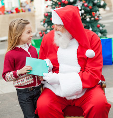 Girl Giving Wish List To Santa Claus