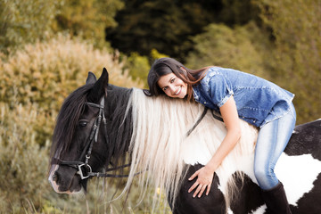 portrait of attractive young female rider embracing her horse
