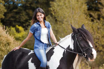 attractive brunette female rider sitting on her horse smiling