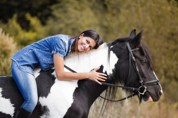 attractive brunette female rider embracing her horse and smiling