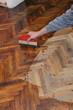 Varnishing of oak parquet floor, workers hand, brush
