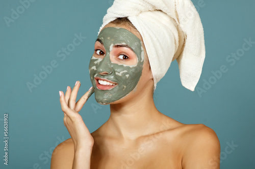 Spa teen girl applying facial clay mask. Beauty treatments.
