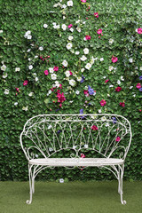 Beautiful white bench next to green hedge with small flowers.