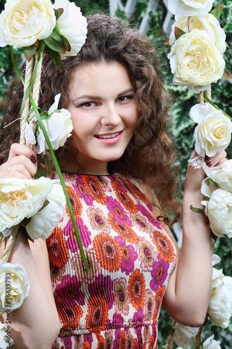 Beautiful smiling woman sits on swing overgrown with white roses
