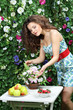 Young woman touches bunch of flowers on table