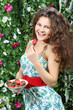 Happy woman holds plate with strawberries and brings one berry