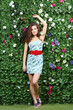Beautiful woman in short dress stands next to green hedge
