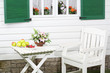 White wooden table with fruits and flowers and chair near house.