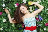 Beautiful happy woman with apple next to green hedge in garden.