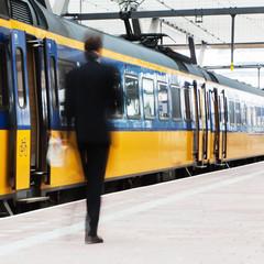 Geschäftsmann in Bewegungsunschärfe auf dem Bahnsteig