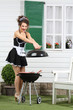 Beautiful housemaid closes lid of barbecue with sausages