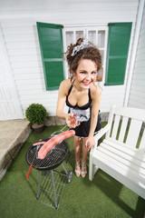 Beautiful housemaid fry sausage on brazier near house