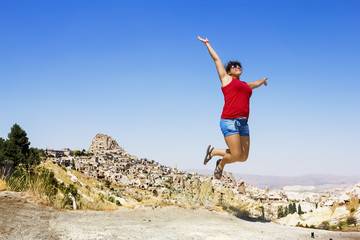Happy girl jumping on the background of the cave city in Cappado